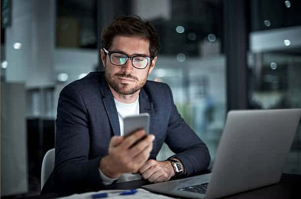 Shot of a young businessman using his laptop and phone at work